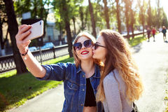 逗人喜爱的相当最好的朋友女孩,拥抱和有乐趣画象一起,亲吻,微笑,喜悦,姐妹 免版税库存照片