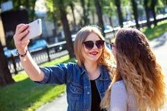逗人喜爱的相当最好的朋友女孩,拥抱和有乐趣画象一起,亲吻,微笑,喜悦,姐妹 免版税库存图片