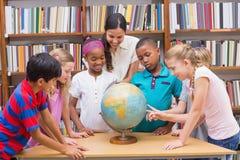 逗人喜爱的看地球的学生和老师在图书馆里 库存图片