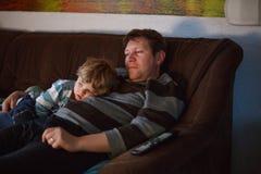 逗人喜爱的看电视的小男孩和他的父亲 免版税库存照片
