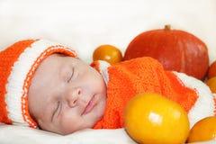 逗人喜爱的睡觉的微笑的新出生的婴孩在一个被编织的桔子穿戴了 库存照片