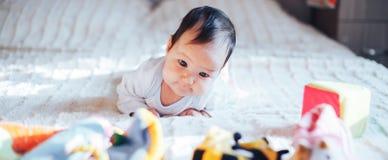 逗人喜爱的矮小的三个月的女婴,在家使用在床上在卧室,软绵绵地在她前面的后面光 免版税库存图片