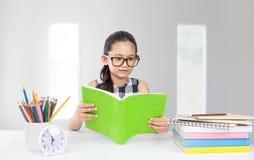 逗人喜爱的矮小的亚洲女孩穿戴玻璃阅读书 免版税库存图片