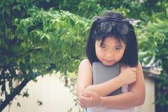 逗人喜爱的矮小的亚裔中国女孩和她的玻璃栖息在她的顶头举行的智能手机顶部在庭院里 免版税图库摄影