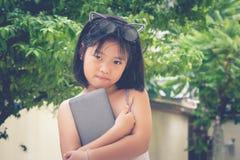 逗人喜爱的矮小的亚裔中国女孩和她的玻璃栖息在她的顶头举行的智能手机顶部在庭院里 库存图片