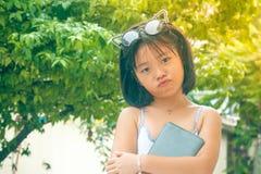 逗人喜爱的矮小的亚裔中国女孩和她的玻璃栖息在她的顶头举行的智能手机顶部在庭院里 免版税库存图片