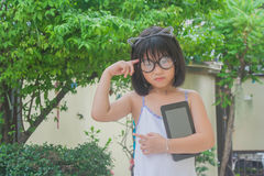 逗人喜爱的矮小的亚裔中国女孩和她的玻璃栖息在她的顶头举行的智能手机顶部 库存照片