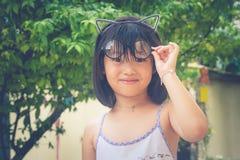 逗人喜爱的矮小的亚裔中国女孩和她的玻璃栖息在她的头顶部 库存图片