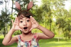 逗人喜爱的矮小的亚裔女孩佩带的兔宝宝耳朵在复活节天 免版税库存图片
