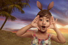 逗人喜爱的矮小的亚裔女孩佩带的兔宝宝耳朵在复活节天 图库摄影