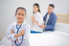 逗人喜爱的矮小的亚裔女孩在家穿戴了象医生 图库摄影