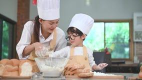 逗人喜爱的矮小的亚裔过滤与过滤器筛子滤锅的男孩和美丽的母亲面团面粉在桌上的家庭厨房里为准备 股票录像