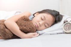 逗人喜爱的矮小的亚洲女孩睡眠和拥抱女用连杉衬裤涉及床 图库摄影