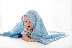 逗人喜爱的矮小的四个月的男婴,在家使用在床上 免版税库存图片