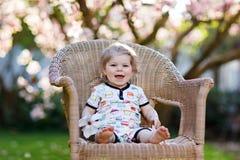 逗人喜爱的矮小的女婴坐大椅子在庭院里 有开花的桃红色木兰树的美丽的愉快的微笑的小孩 免版税库存照片