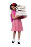 逗人喜爱的矮小的女小学生运载的堆书 免版税库存图片
