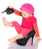 尝试在她的在白色后面的母亲的鞋子的逗人喜爱的矮小的女婴 免版税库存图片