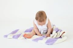 逗人喜爱的矮小的女婴坐与被隔绝的格子花呢披肩的地板 免版税库存图片