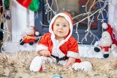 逗人喜爱的矮小的婴孩在圣诞老人衣裳 库存图片