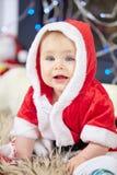 逗人喜爱的矮小的婴孩在圣诞老人衣裳 免版税库存照片