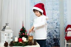 逗人喜爱的矮小的学龄前男孩圣诞节画象,吃曲奇饼 免版税库存图片