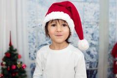 逗人喜爱的矮小的学龄前男孩圣诞节画象,吃曲奇饼 库存图片