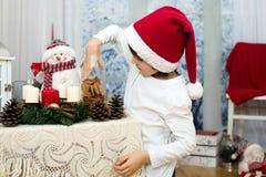 逗人喜爱的矮小的学龄前男孩圣诞节画象,吃曲奇饼 图库摄影