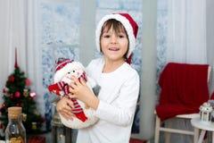 逗人喜爱的矮小的学龄前男孩圣诞节画象,吃曲奇饼 库存照片