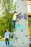 逗人喜爱的矮小的学龄前男孩,上升在有绳索的岩石墙壁上 免版税库存照片