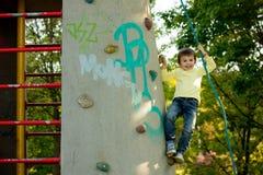逗人喜爱的矮小的学龄前男孩,上升在有绳索的岩石墙壁上 免版税库存图片