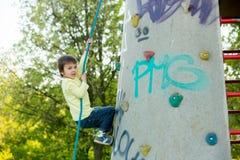 逗人喜爱的矮小的学龄前男孩,上升在有绳索的岩石墙壁上 库存照片
