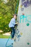 逗人喜爱的矮小的学龄前男孩,上升在有绳索的岩石墙壁上 库存图片