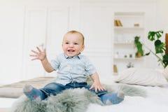 逗人喜爱的矮小的小孩男孩坐床 免版税库存照片