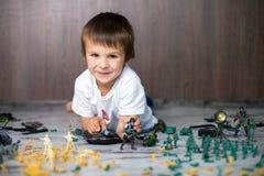 逗人喜爱的矮小的小孩男孩,在家使用与战士和figur 免版税图库摄影