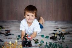 逗人喜爱的矮小的小孩男孩,在家使用与战士和figur 免版税库存照片
