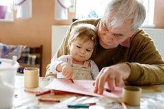 逗人喜爱的矮小的小小孩女孩和英俊的资深祖父绘画与五颜六色的铅笔在家 孙和人 免版税图库摄影