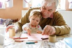 逗人喜爱的矮小的小小孩女孩和英俊的资深祖父绘画与五颜六色的铅笔在家 孙和人 库存照片