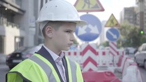 逗人喜爱的矮小的成功的男孩佩带的西装和安全设备和建设者在一条繁忙的路的盔甲身分  股票视频