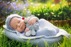 逗人喜爱的矮小的新出生的男婴,睡觉,举行逗人喜爱矮小mous 库存照片