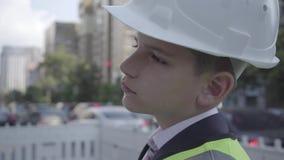 逗人喜爱的矮小的沉思男孩佩带的西装和安全设备和建设者在一条繁忙的路的盔甲身分在a 影视素材