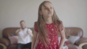 逗人喜爱的矮小的滑稽的女孩画象红色礼服跳舞的在蓬松地毯的前景 有胡子的父亲开会 股票录像