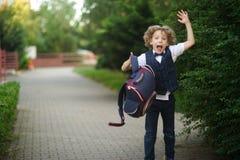 逗人喜爱的矮小的男小学生,挥动他的在校园的公文包 库存图片