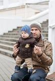 逗人喜爱的矮小的男婴和他的父亲 库存图片