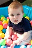 逗人喜爱的矮小的男婴获得乐趣在球坑 库存图片