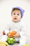 逗人喜爱的矮小的白种人男孩11个月坐并且吃在白色背景的红色苹果 免版税库存照片