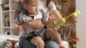 逗人喜爱的矮小的白肤金发的女婴使用与与坐塑料的鱼的大兴趣在她的妈妈的接受慢动作 影视素材