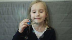 逗人喜爱的矮小的白肤金发的女孩吹的空气肥皂泡 股票视频