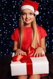 逗人喜爱的矮小的白肤金发的女孩圣诞节照片拿着礼物-在假日光亮的ligh backgroud的箱子的圣诞老人帽子和红色礼服的  免版税库存图片