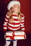 逗人喜爱的矮小的白肤金发的女孩圣诞节照片拿着礼物-箱子的圣诞老人帽子和红色礼服的 免版税库存照片