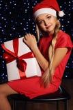 逗人喜爱的矮小的白肤金发的女孩圣诞节照片拿着礼物-箱子的圣诞老人帽子和红色礼服的 免版税图库摄影